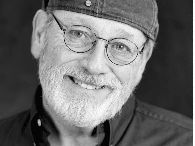 A kindly, older man with a short white beard, wearing a backwards cap and wire-rimmed glasses, smiles at the camera.