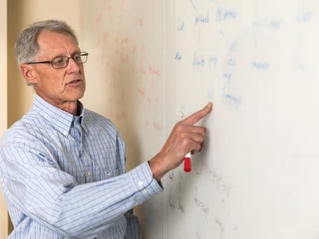 An NAU professor is pointing at a board while lecturing to his students