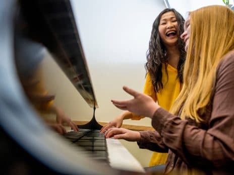 a student receives piano lessons from a laughing faculty member