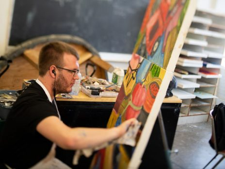 An NAU art student is painting on a canvas