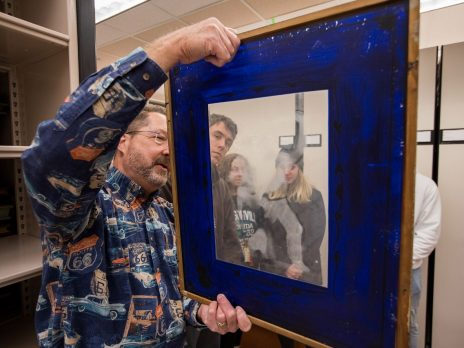 An NAU professor is holding a framed picture and inspecting it closely