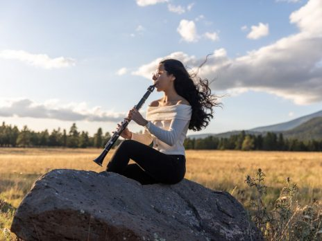 An NAU student playing a flute in the outdoors of Flagstaff