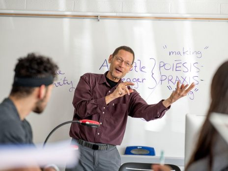 An NAU philosophy teacher is explaining a concept to his students