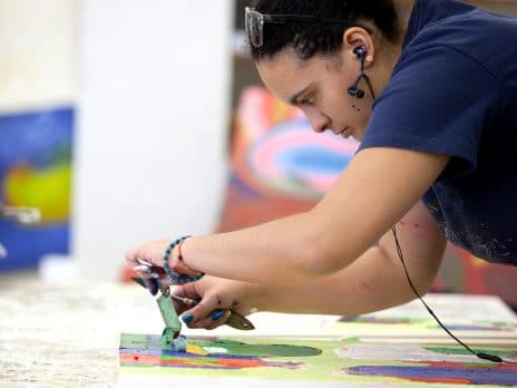 a female art student works on a painting