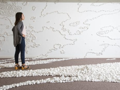 a student examines an art installation of white-painted rocks winding along the floor and up the walls