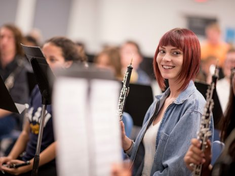 student smiles at camera while holding a clarinet
