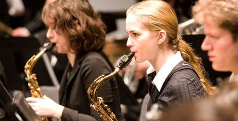 two women playing saxophone amongst other band members