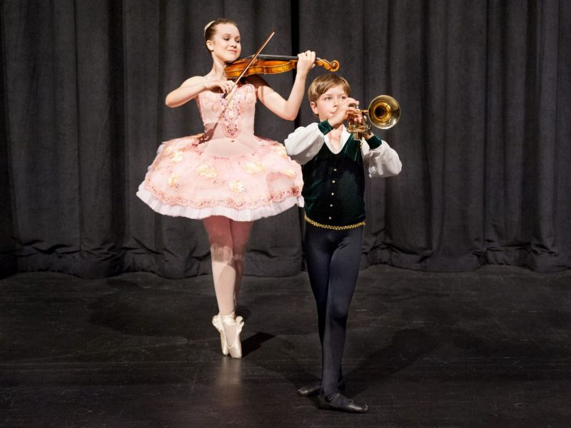two young children play instruments on stage