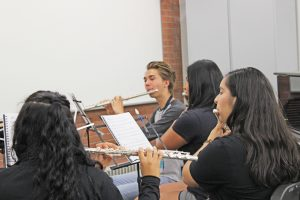 several students play the flute in school of music classroom