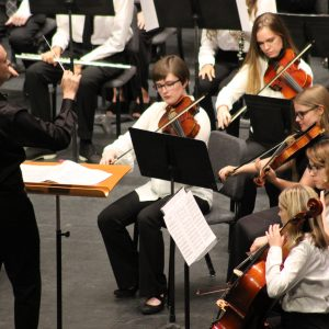 several students playing violin through instruction of conductor