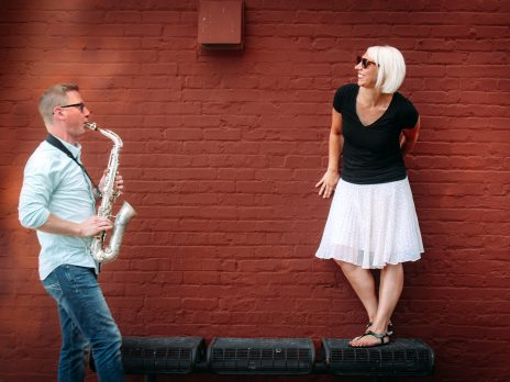 man and woman stand in front of a red brick wall while man plays a saxophone