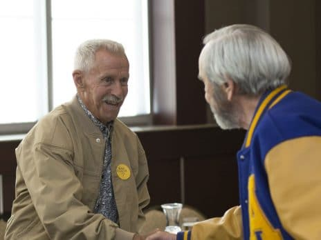 Two NAU Alumni shake hands at the Cafe Au Louie Homecoming 2016