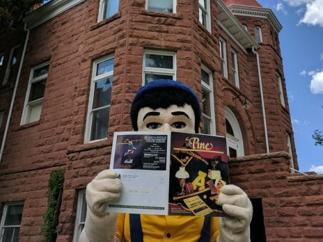 Louie the Lumberjack reads Pine magazine in front of Old Main.