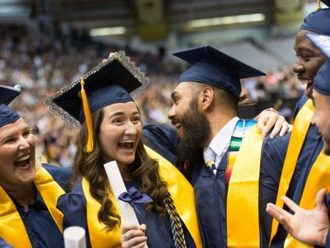 NAU students hugging after receiving their diploma at commencement.