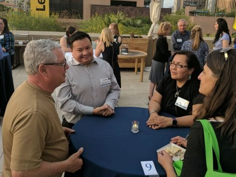 NAU alumni sit at an outdoor table and converse at the Phoenix chapter career networking