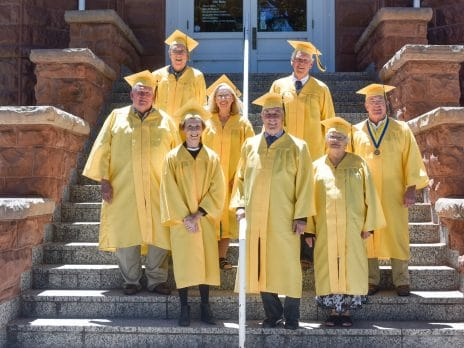 nau alumni class of 1967 wearing caps and gowns on steps of old main