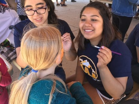 Two Lumberjack Alumni Ambassadors paint a students face at a LAA Club meeting.