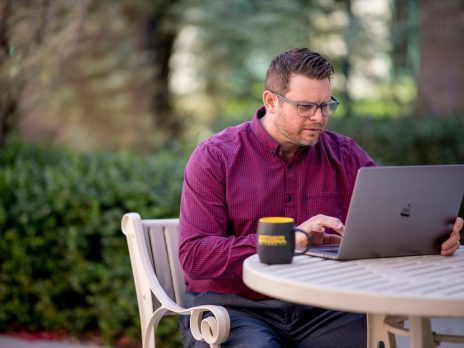 man in red shirt sitting at a table outdoors using a laptop