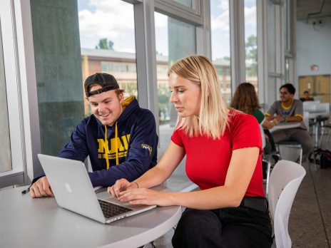 Students studying at a table and smiling