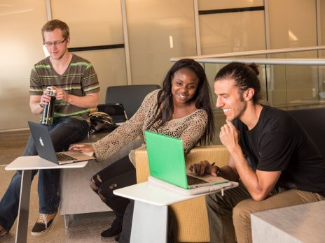 Students studying together and looking at a laptop