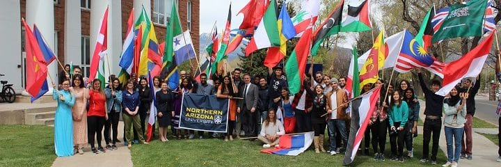 A group of students waving flags from various countries with an NAU banner in the center