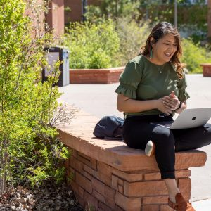 A student with a laptop at NAU campus.