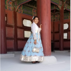 Student in a dress posing against a building