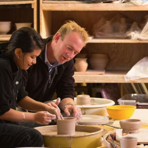 Student and teacher working on a ceramic pot