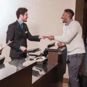 Man handing another man a hotel key across a desk