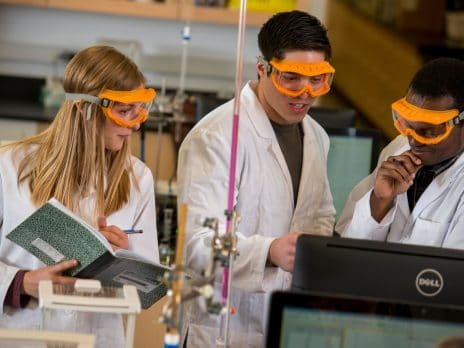 Three NAU graduate students conduct research during lab hours wearing white coats and goggles.