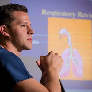 Male student in scrubs looking off into the distance with a slide of the human respiratory system in the background