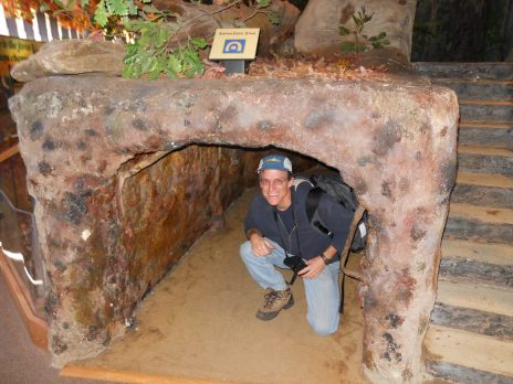 man kneeling inside of small cave indoors