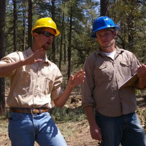 two men wearing hard hats while standing in a forest talking