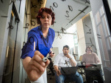 instructor writes on glass while students watch