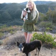 Ginger Christenson holding her dogs in the desert.