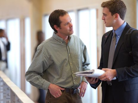 business student dressed in a suit is talking with an instructor in the NAU business building