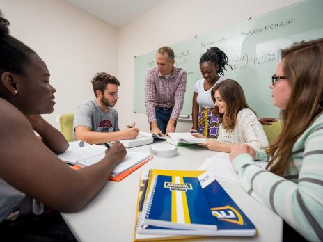 five math students being tutored by professor in a classroom