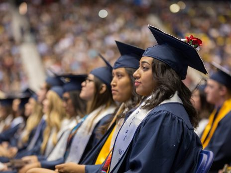 students wearing caps and gowns, seated, looking forward at graduation