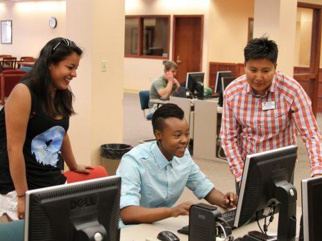 three nau students working on a computer