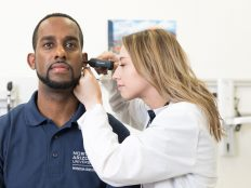 An ear examination being done on a patient by an NAU Physician Assistant student.