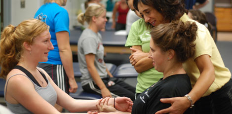 Female NAU PT Students with Professor as they practice rehab techniques
