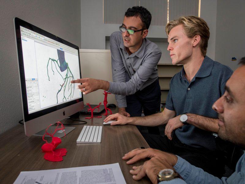 photo of nau mechanical engineering students gathered around a computer
