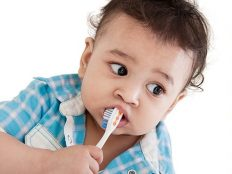 Young child holding a toothbrush in his mouth attempting to brush his teeth.