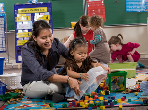 photo of children playing with blocks in a classroom with adult help