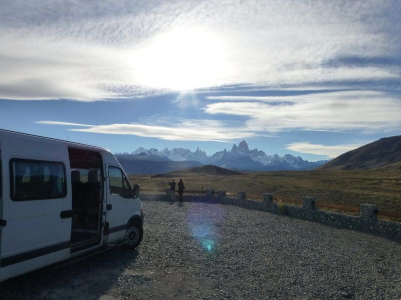 A view of the mountains with a van parked on the side