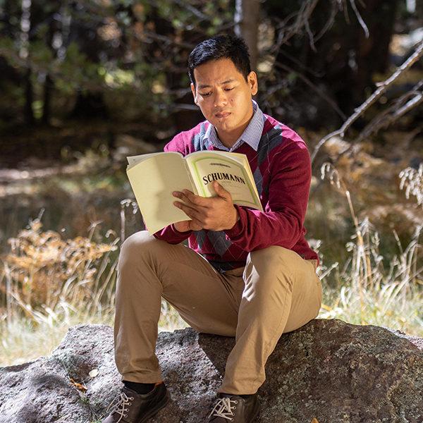 Ye Lynn Han sitting on a rock outdoors, reading
