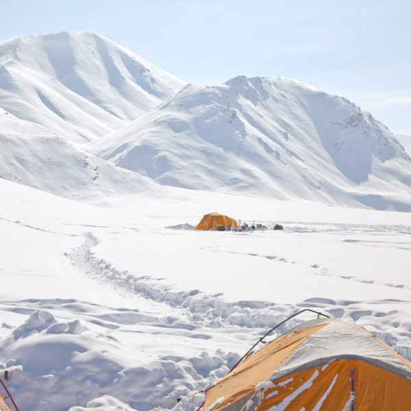 A bright orange tent in the distance of an Arctic landscape