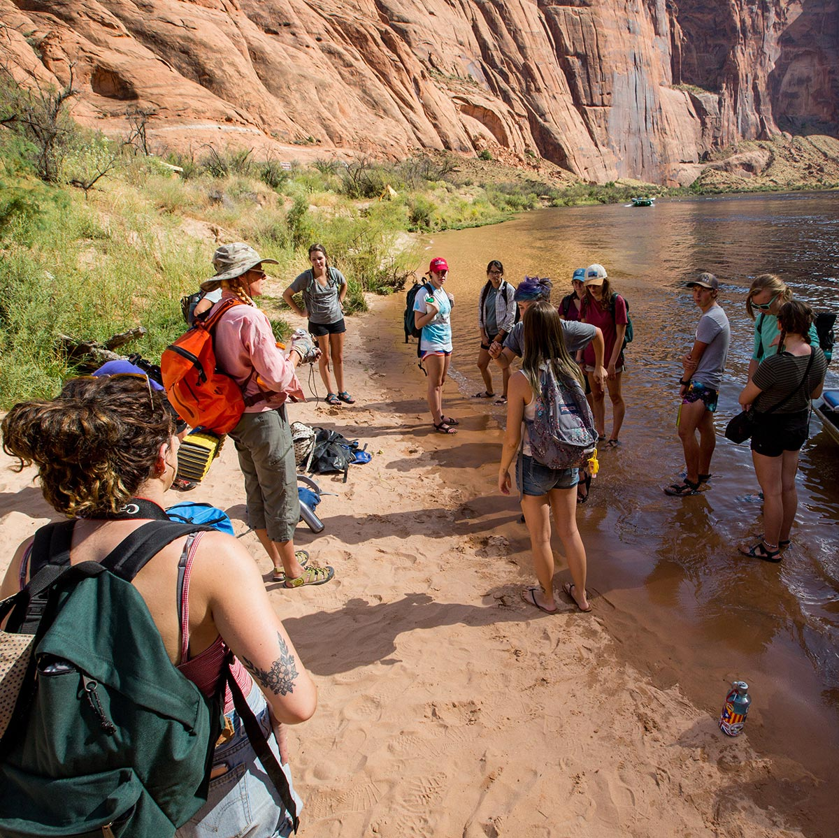 Students and an instructor stand on the edge of a body of water at the Colorado Plateau