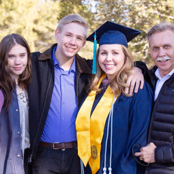 A young woman in graduation regalia surrounded by her family
