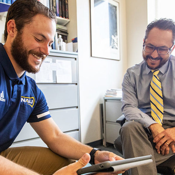A young man in an NAU polo consults a tablet with a professor in his office